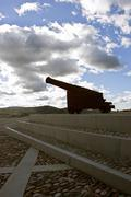 silhouette of canon of iron in urban layout with cloudy blue sky - stock photo