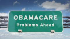 Obamacare problems ahead road sign Stock Footage