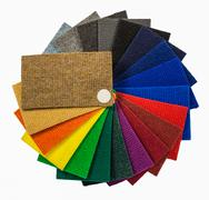 Multi-colored carpeting samples by a fan Stock Photos