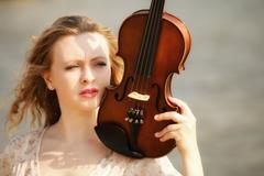 portrait blonde girl with a violin outdoor - stock photo