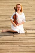 the blonde girl with a violin outdoor - stock photo