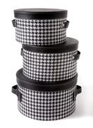 Set of houndstooth check and black leather bandboxes Stock Photos