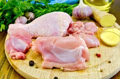 chicken leg cut on a wooden board with ginger - stock photo