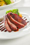 oven crisp duck breast marinated.in a peking duck style sauce on a tian of po - stock photo