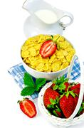 Cornflakes with milk in a jug and strawberries Stock Photos