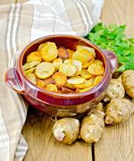 jerusalem artichokes fried in a pan on the board - stock photo