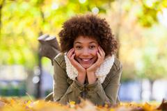 autumn outdoor portrait of beautiful african american young woman lying down  - stock photo