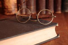 old eyeglasses on bookshelf - stock photo