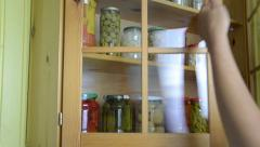 Hand open cupboards door take all jars from the underneath shelf Stock Footage