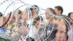 Barbed wire with people on background, click for HD Stock Footage