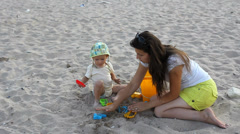 Beautiful baby boy and mother play with sand plastic toys on the seashore Stock Footage