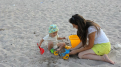 Baby and mother sit on seashore sand and play with colorful sea toys Stock Footage