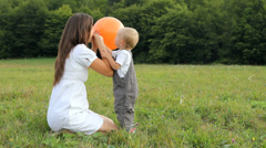 Mother inflate colorful balloon, baby anxious to play, happy memories in nature - stock footage
