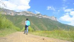 Traveler walking on a rough road before beautiful Gemu holy mountain Stock Footage