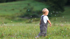 Lovely baby have fun, run to catch the soap bubbles, water baloons Stock Footage