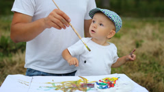 Family view, cute baby son and father paint with brush outdoor, first drawing Stock Footage