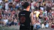 Stock Video Footage of Male fire artist with burning pois bows finishing performance, click for HD