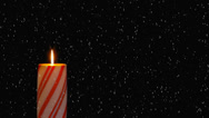 Stock Video Footage of Snowing on a glowing red holiday candy cane candle.