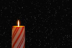 Snowing on a glowing holiday candy cane candle. Stock Footage