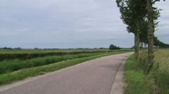 Dike along feeder canal + pan traditional dome-shaped farm in low-lying polder Stock Footage