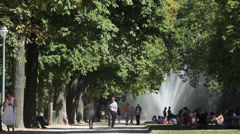 People in park with green trees and artesian fountain, Brussels, Belgium park Stock Footage