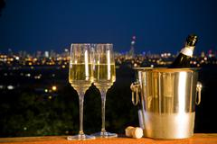 Champagne bottle and two glasses with night skyline in backgroun Stock Photos