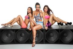 sexy girls sitting on large speaker - stock photo