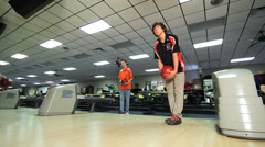 Bowler rolls ball down lane Stock Footage