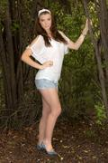 Stock Photo of beautiful young girl with white top and short pants standing in a bush