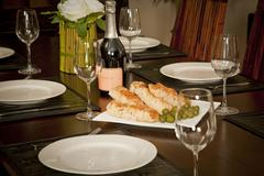 Wooden table dinner setting with bread olives and wine Stock Photos