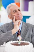 thinking senior man with birthday cake - stock photo