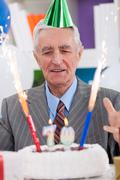 excited senior man looking at his birthday cake - stock photo