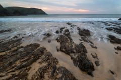 Hope cove sunset landscape seascape with rocky coastline and long exposure Stock Photos