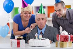 Senior man blowing in  the candles on cake Stock Photos