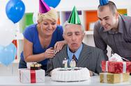Stock Photo of senior man blowing in  the candles on cake