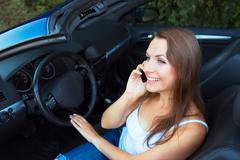 Stock Photo of smiling caucasian woman talking on phone in a cabriolet