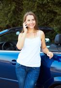 smiling caucasian woman talking on phone in a cabriolet - stock photo