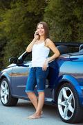Smiling caucasian woman talking on phone in a cabriolet Stock Photos