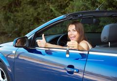 smiling caucasian woman showing key in a cabriolet - stock photo