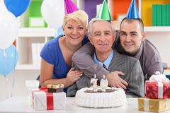 portrait of happy family on 70th birthday - stock photo