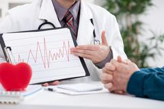 Cardiologist showing ekg results Stock Photos