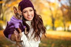 Stock Photo of woman holding her puppy after in the park