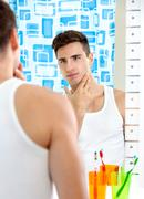 man looks at himself in mirror - stock photo