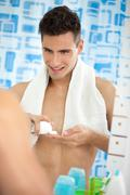 young man in the bathroom's mirror with shave foam on hand - stock photo