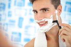 Man shaving his beard with razor Stock Photos
