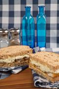 fresh fish finger sandwich on wholegrain in rustic kitchen setting - stock photo