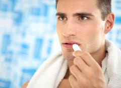 Man  applying balsam for lips Stock Photos