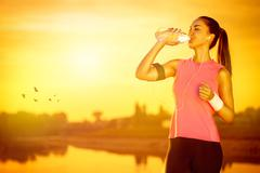 female jogger drinking water - stock photo