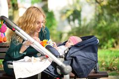 mother with baby in pram - stock photo