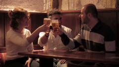 Three friends toasting beer in a pub Stock Footage